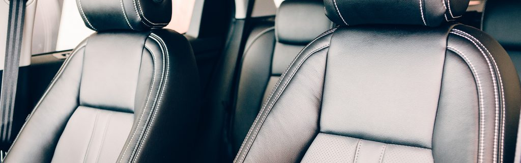 Cropped view of the seats in black handmade leather in the interior of an elegant car